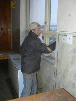 Pán Jozef Vrábeľ opravuje tesnenie okien v sále kultúrneho domu Vojkovce