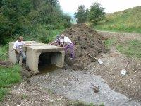Pán Kandrik František , Miroslav Legát a Bandžuch Ladislav pripravujú osadenie mosta v koryte potoka