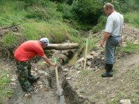 Pán Legát Miroslav a Kandrik Fero vytýčuju prechod potrubia obecného vodovodu cez potok